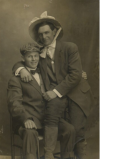 Man in Easter bonnet hugging another man; vintage gay