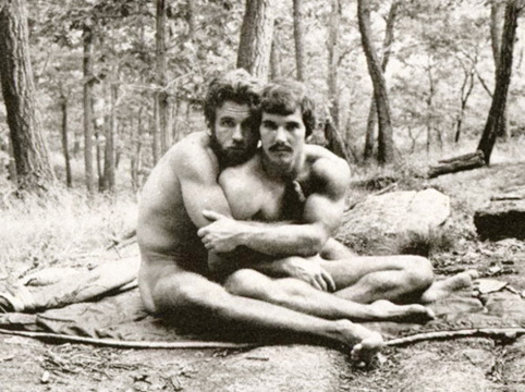 Two gay men hug in the woods
