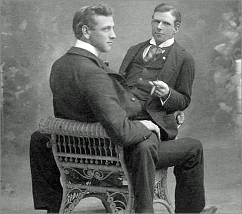 One man seated on the lap of another; vintage gay photo, gay marriage