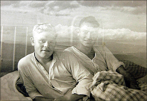 Two men in bed, vintage gay photo set against double exposure of open range