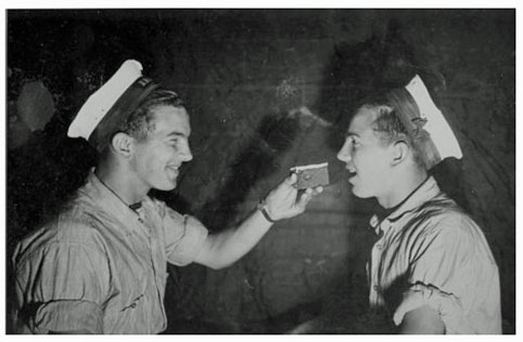 One sailor feeds cake to another. Vintage, gay